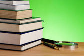 Pile of books, pen and magnifier on table — Stock Photo