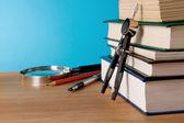 Penna, pila di libri e lente d'ingrandimento sul tavolo in legno — Foto Stock