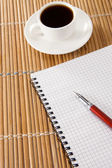 Pen on notebok and cup of coffee — Стоковое фото