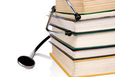Pile of books and stethoscope isolated on white — Stock Photo