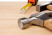 Hammer and tape measure on wood — Stock Photo