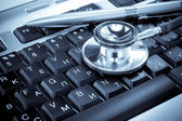 Shiny stethoscope and pen on keyboard — 图库照片