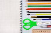 Pennen, potloden en schaar op raster grafiekpapier — Stockfoto