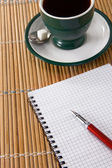 Cup of coffee and ink pen with checked notebook on straw — Stock Photo