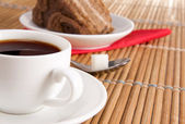 Cup of coffee and sweet pie on wood straw — Stock Photo