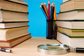 Pile of books, magnifier and holder with pencil — Stock Photo