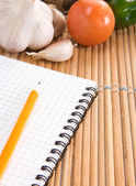 Notebook, garlic and tomato with pencil in kitchen — Stock Photo