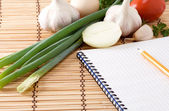 Notebook with pencil, garlic, tomato and onion on straw — Stock Photo