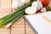 Notitieboekje met potlood, knoflook, tomaten en uien op stro — Stockfoto