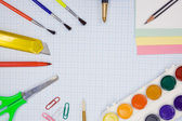 Pens, pencils, paint brush and scissors on graph grid paper — Стоковое фото