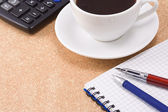 Pen, pencil and cup of coffee on notebook — Stock Photo