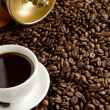 Cup of coffee and spoon on roasted beans — Stockfoto