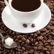 Cup of coffee and spoon on roasted beans — Stock Photo #12343593