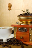 Cup full of coffee, beans, pot and grinder — Stock Photo