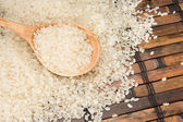 Rice and wood spoon on table — Stock Photo