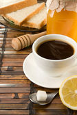 Coffee, honey and bread on table — Stock Photo