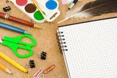 School accessoires en geselecteerde notitieblok op hout — Stockfoto