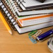 Stock Photo: Pile of notebook and pens on wood background