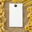 Raw pasta and price tag on sack hessian — Stock Photo
