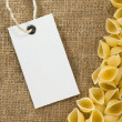 Raw pasta and price tag on sack hessian burlap — Stock Photo