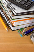 Pile of notebook and pens on wood background — Стоковое фото