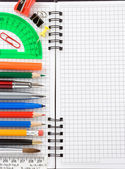 School accessories and supplies on checked notebook — Stock Photo