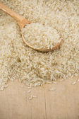 Uncooked rice seed and wood spoon — Stock Photo