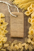 Raw pasta and price tag on woo — Stock Photo