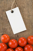 Price tag and tomato vegetable at wood background — Stock Photo