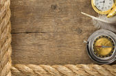 Ship ropes and compass with feather at old wood — Stock Photo