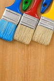 Colorful paintbrush on wood background — Stock Photo