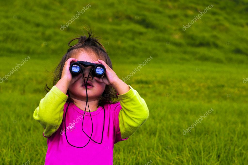 Little girl looks through binoculars. — Stock Photo #10779365