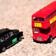 Foto Stock: A bright red traditional London Bus and Black Taxi isolated over tar-seal.