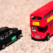 A bright red traditional London Bus and Black Taxi isolated over tar-seal. — Stock Photo