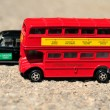Stock Photo: A bright red traditional London Bus and Black Taxi isolated over tar-seal.