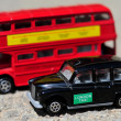 A bright red traditional London Bus and Black Taxi isolated over tar-seal. — 图库照片