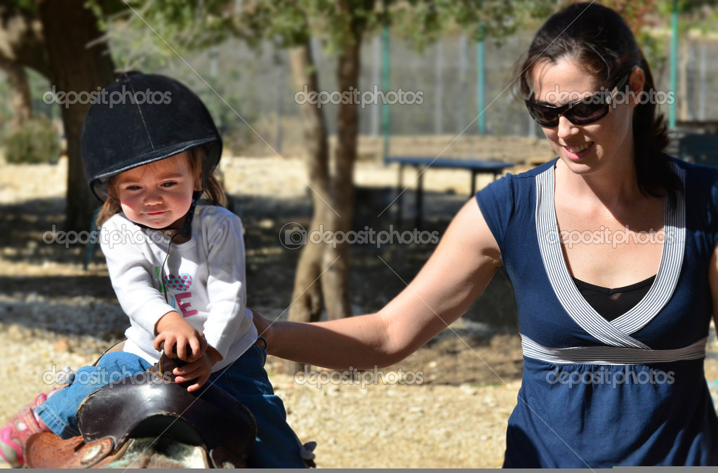A baby girl rides pony horse. — Stock Photo #10853381