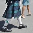 A man dressed up a Scottish kilt and a woman wearing a dress walk down the street. — Stock Photo