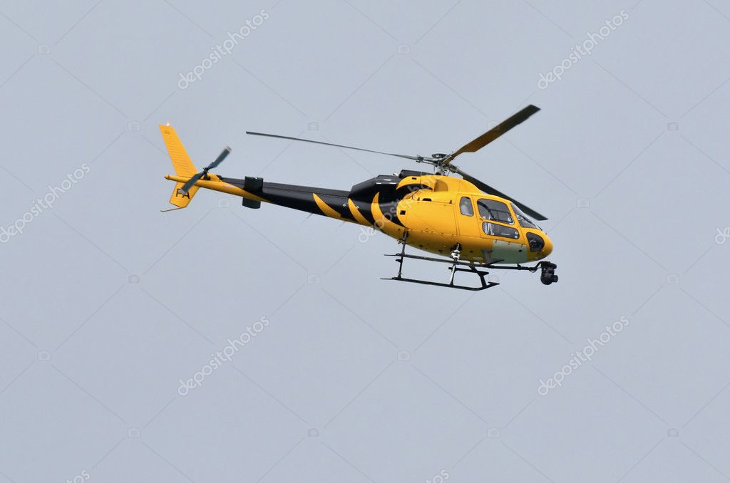 A black and yellow helicopter on blue sky with TV camera. — Stock Photo #10943827