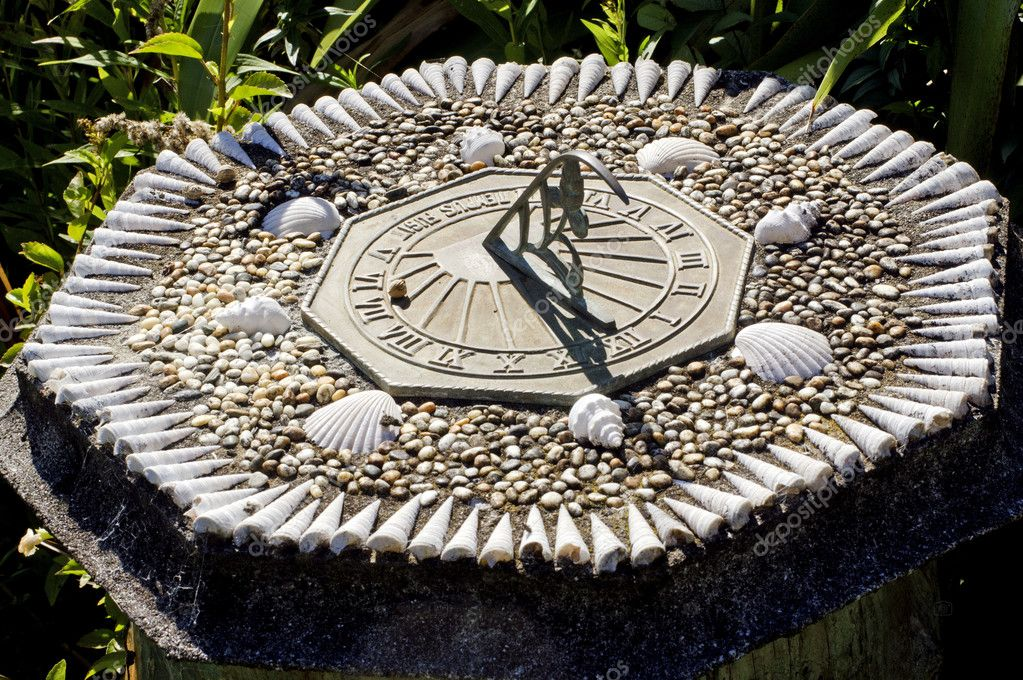 An old sun clock made by seashells dial in a garden. — Stock Photo #10945397