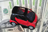 Black and red car over a lot of dollar bills isolated on white (selective focus) — Stock Photo