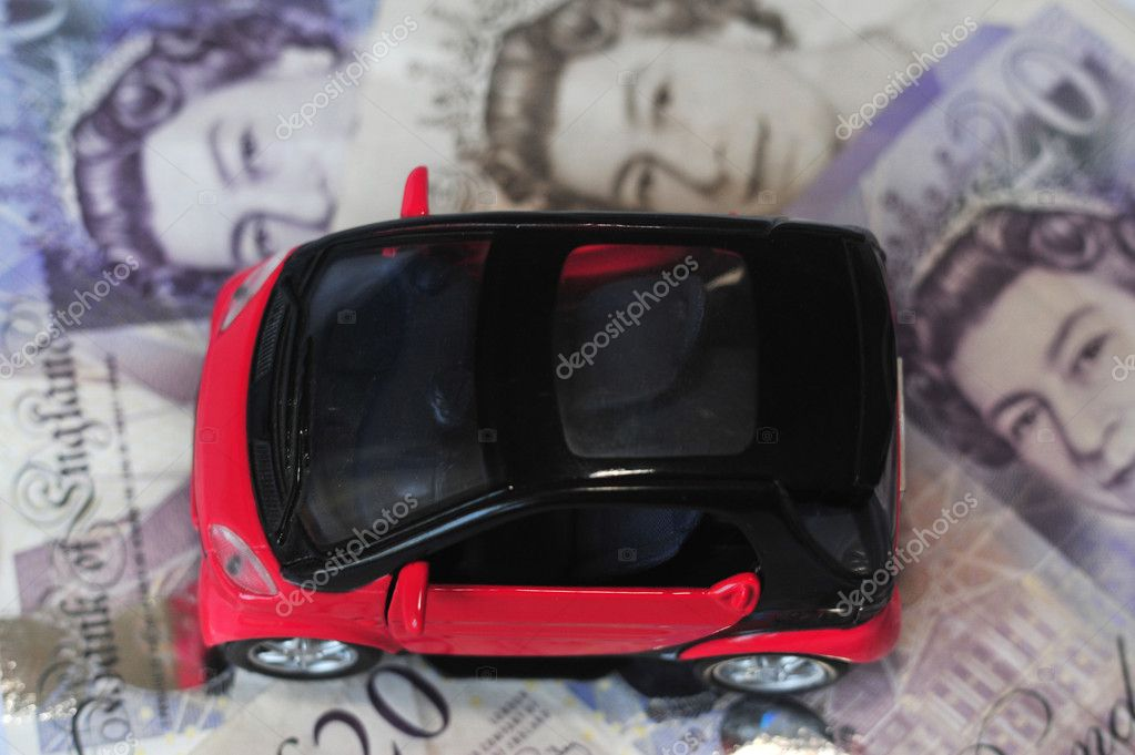 Black and red car over a lot of British Pound Sterling bills isolated on white (selective focus).  Stock Photo #11134725