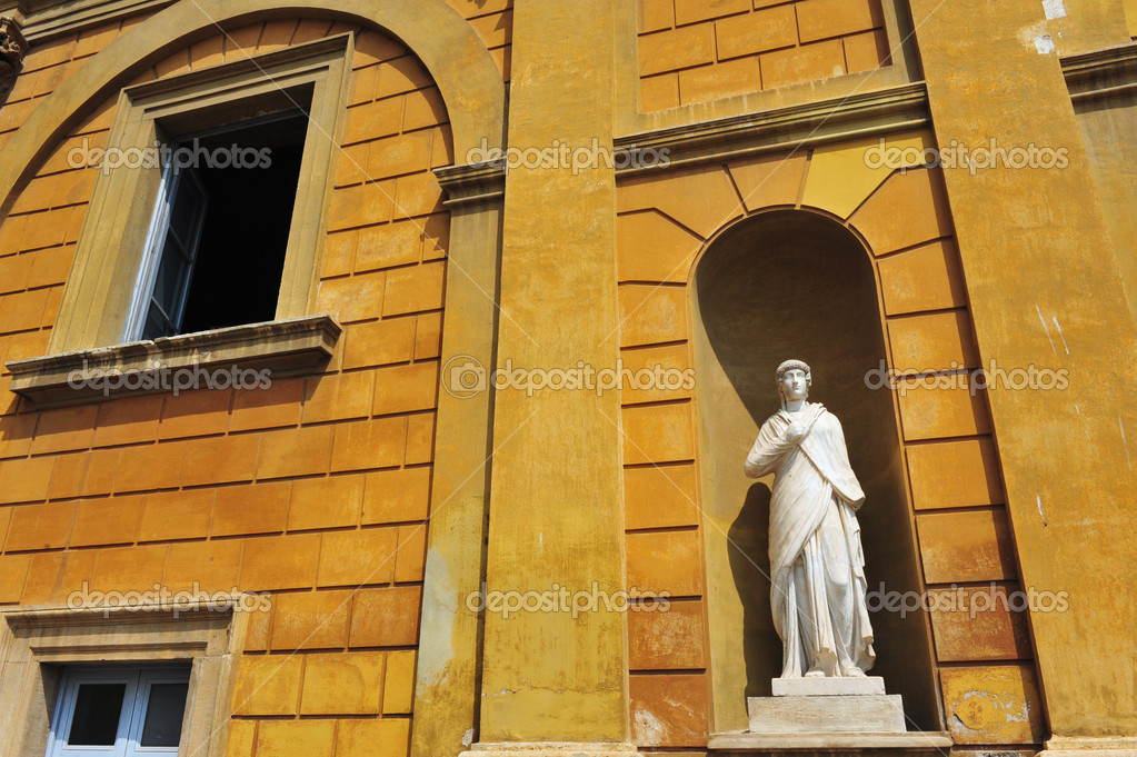 A man looks outside a window near a Roman statue in the Vatican museum, Rome, Italy.  Stock Photo #11134793