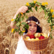 Girl Holds Basket of Fruit in Field of Wheat — Stock Photo
