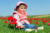 Baby Girl Sitting in Flowery Field — Stock Photo