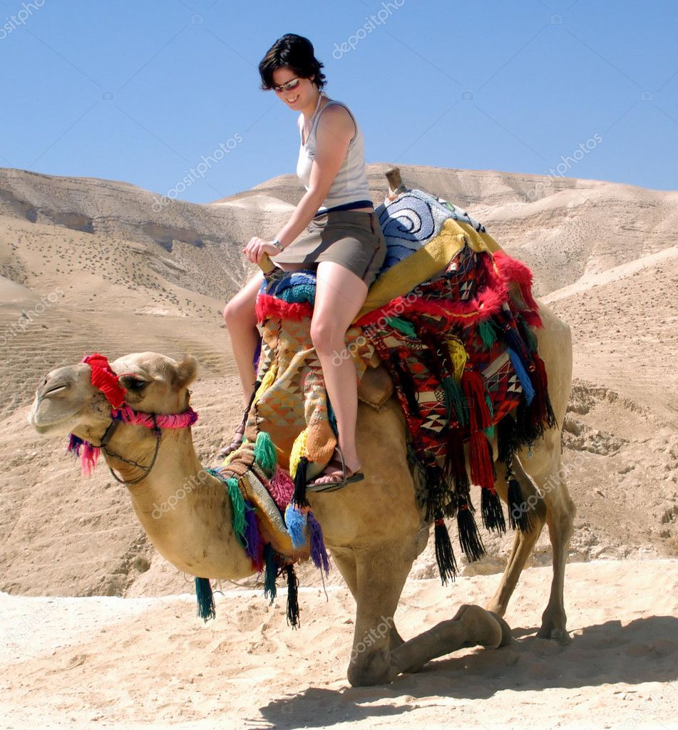 A young woman tourist rides a camel for the first time in the Judean desert near the Dead Sea in Israel — Stock Photo #11142630