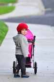 Little girl with stroller — Stock Photo