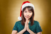 Girl with santa hat greeting — Stock Photo