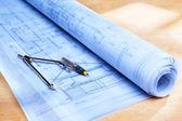 Blueprint on wooden desk — Stock Photo