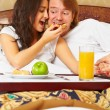 Couple enjoying breakfast on bed — Stockfoto